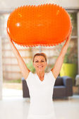 Happy middle aged woman holding an exercise ball — Stock Photo