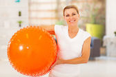 Fit mature woman holding exercise ball at home — Stock Photo