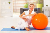 Happy senior woman resting on mat after exercise at home — Stock Photo