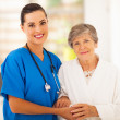Stock Photo: Senior womand caring young nurse