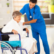 Friendly caregiver helping senior woman on wheelchair — Stock Photo