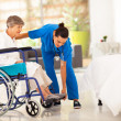 young caregiver helping elderly woman on wheelchair — Stock Photo