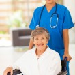 Stock Photo: Pretty young nurse pushing senior woman on wheelchair