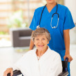 Pretty young nurse pushing senior woman on wheelchair — Stock Photo