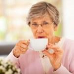 äldre kvinna dricker te hemma — Stockfoto