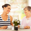 Young woman visiting senior mother and having coffee together — Stock Photo