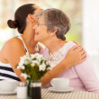 Young woman hugging senior mother when visiting her — Stock Photo
