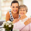 Stock Photo: Pretty woman and senior mother at home