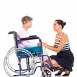 Loving daughter talking to disabled senior mother on white background — Stock Photo