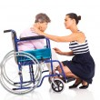 Young woman comforting disabled senior mother on white — Stock Photo