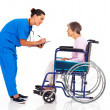 Caring nurse helping senior patient filling medical form — Stok fotoğraf