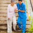 Caring nurse helping senior patient walking down stairs - Photo
