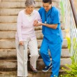 Caring nurse helping senior patient walking down stairs - ストック写真