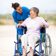 Caregiver talking to disabled senior woman outdoors — Stock Photo