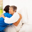 Happy elderly woman hugging caregiver on bed — Stock Photo