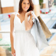 Attractive young woman carrying shopping bags in mall — Stock Photo #19567925