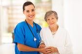 Senior frau und fürsorgliche junge krankenschwester — Stockfoto