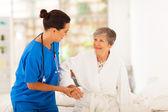 Casero cuidador ayudando a senior mujer levantarse — Foto de Stock