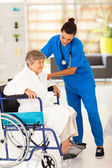 Friendly caregiver helping senior woman on wheelchair — Stock Photo