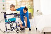 νέοι φροντιστής βοηθώντας ηλικιωμένη γυναίκα σε αναπηρική καρέκλα — Φωτογραφία Αρχείου