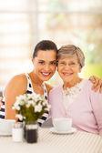 Birlikte kahve içmeye büyükannesinin ve genç ve güzel kadın — Stok fotoğraf