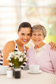 Pretty young woman and grandmother having coffee together — Stok fotoğraf