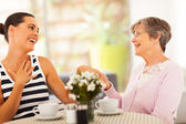 Senior grandmother looking at granddaughter's new ring — Stockfoto