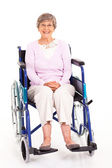 Happy elderly woman sitting on wheelchair isolated on white — Stock Photo