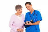 Friendly young nurse helping senior woman with medical form — Stock Photo