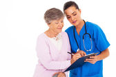 Senior woman signing medical form with help from nurse — Stock Photo