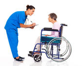 Caring nurse helping senior patient filling medical form — Stock Photo