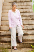 Lonely senior woman standing by stairway — Stock Photo