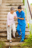 Enfermera cuidando ayudando a senior paciente bajar las escaleras — Foto de Stock