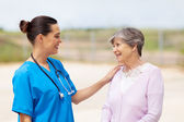 Happy young nurse talking to senior woman outdoors — Stock Photo