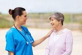 Happy young nurse talking to senior woman outdoors — Stock Photo