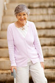 Happy elderly lady standing by stairway with cane — Stock Photo