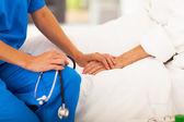 Lekarz gospodarstwa rąk starszego pacjenta i ją pociesza — Zdjęcie stockowe