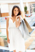 Attractive young woman carrying shopping bags in mall — Stock Photo