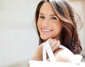 Happy young woman carrying shopping bags on her shoulder — Stock Photo