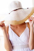 Fun young woman covering her face with summer hat — Stock Photo