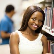 Cute african american college girl reading in library — Stock Photo
