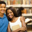 Happy african college couple in library — Stock Photo