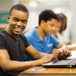 Happy male african college student using laptop in library — Stock Photo #20130723