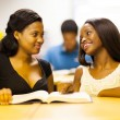 Two african college girls reading book in library — Stock Photo