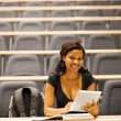 Female african american college student in lecture hall with tablet computer — Stock Photo