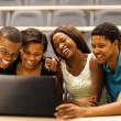 Group of african american college students using laptop in lecture room — Stock Photo