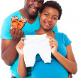 Happy african american expecting couple holding baby clothes and shoes — Stock Photo