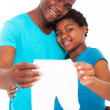 Expecting african american couple holding baby clothes — Stock Photo #20131301