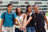 Group of african college students putting hands together — Stock Photo
