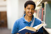 Male african american college student reading book in library — Stok fotoğraf